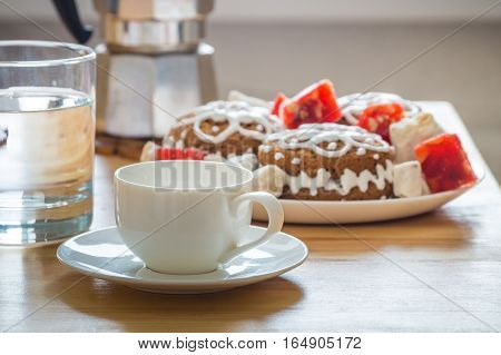 Holiday breakfast serving. Espresso cup, cookies and sweets, glass of water and italian moka coffee pot on natural wood table served for a christmas breakfast