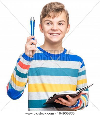 Portrait of caucasian smiling teen boy with notebook and blue pen writing something. Handsome funny teenager, isolated on white background. Happy student making idea gesture.