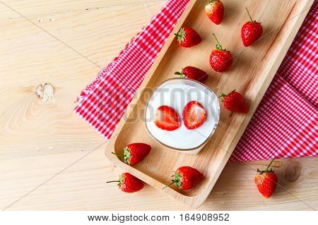Closed up strawberry yogurt in the glass on a wooden backgroundwith healthy flat lay.