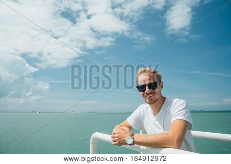 Portrait of a young successful man on the background of sky and sea landscape. Blonde with glasses in white shirt leaning on the railing of the ship.