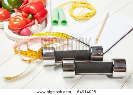 Sport and diet. Healthy lifestyle. Vegetables, dumbbells and notebook. Peppers, tomatoes, garlic, onion and radish in a heart on a white background