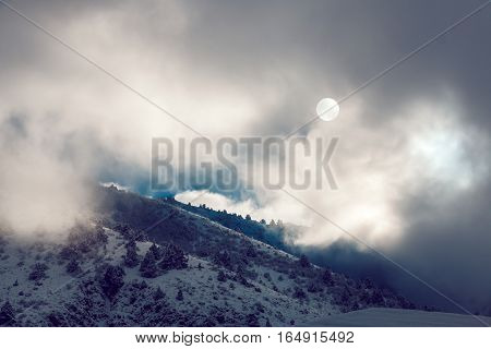 Dramatic pictersque landscape of snowy winter mountains partially covered by clouds with cold winter sun
