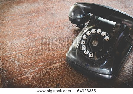 Black Antique Vintage Analog Telephone Dialing Or Scrolling Phone On Wooden Table. Contact Us Concep