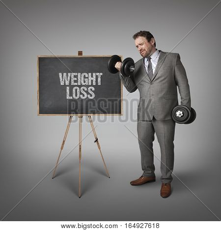 Weight loss text on blackboard with businessman holding weights
