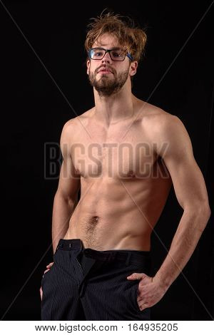 handsome bearded athletic macho man with stylish beard standing in glasses with muscle torso on athletic body with both hands in his pocket in studio on black background