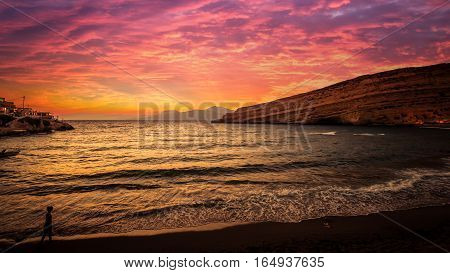 Stunning sunset at Matala beach on Crete island, Greece. There is a girl walking on the beach. The colors in the sky are very beautiful, yellow, orange and red.
