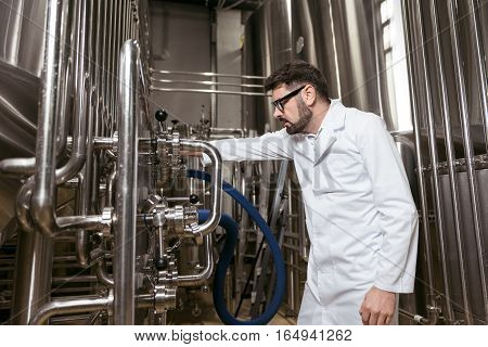 Part of process. Concentrated handsome young man working with brewing mechanism while spending time at factory and making beer.