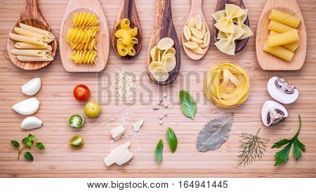 Italian Food Concept .various Kind Of Pasta In Wooden Spoons With Ingredients Sweet Basil ,tomato ,g