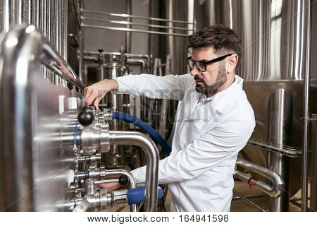 Perfect worker. Smart young handsome man using brewing mechanism while spending time at factory and making beer.