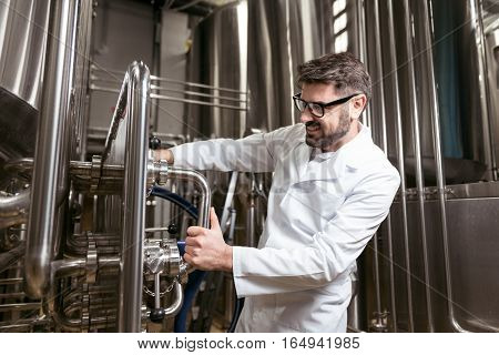 Ideal worker. Delighted young handsome man using brewing mechanism while spending time at factory and making beer.