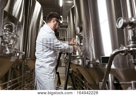 Professional worker. Concentrated young handsome man using ladder while spending time at factory and making beer.