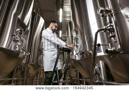I am professional. Serious young handsome man using ladder and brewing mechanism while working at factory and making beer.