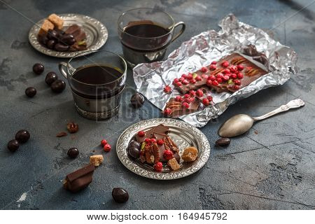 coffee in vintage silver cups on a dark background with chocolate. Close view.
