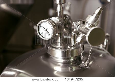Controllable process. Close up of measuring gauge and pipes being used in brewery.