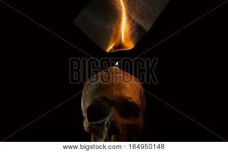 Burning handwritten letter by candle fire on skull sculpture