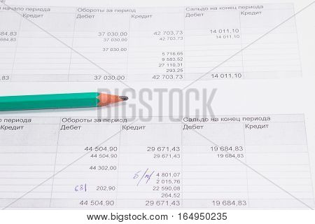 a pencil lying on a document it's accounting report that shows the amount of