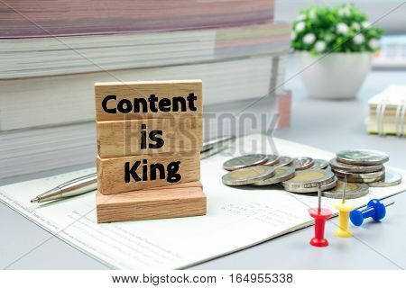 Text message Content is king on wooden with book bank, stacked coins. Finance concept