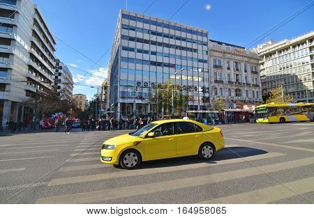 SYNTAGMA ATHENS GREECE, DECEMBER 18 2016: yellow taxi and people waiting to cross the road at Syntagma Athens Greece. Editorial use.