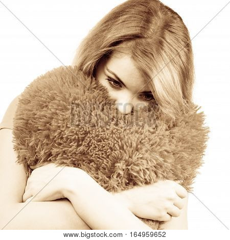 Woman blonde sad unhappy girl hugging heart shaped big pillow studio shot on white. Heartbroken young female.