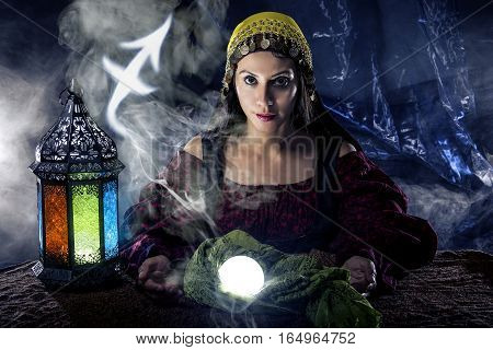 Psychic or fortune teller with crystal ball and horoscope zodiac sign of Sagitarius