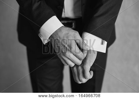 man correct sleeves on shirt hands close-up dressing man's style