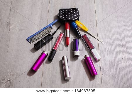 Beautiful cosmetic bag with polka dots with make-up copyspace on a wooden background . Lipsticks and nail polishes