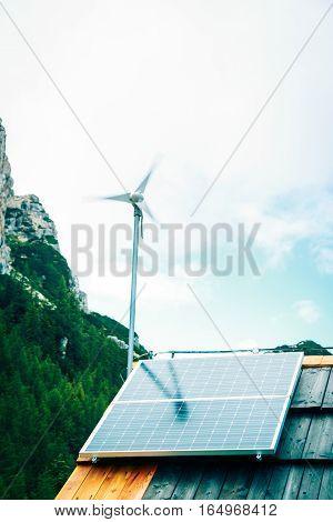 wind turbine and solar panel on mountain hut