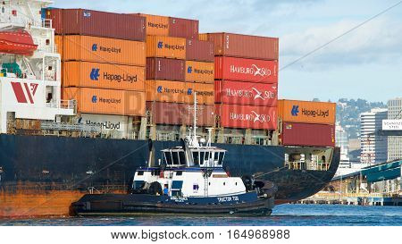Oakland CA - January 01 2017: Tugboat AHBRA FRANCO at the port quarter of cargo ship SEASPAN FELIXSTOWE assisting the vessel to maneuver into the Port of Oakland.