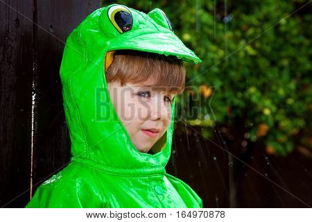 A young boy in a green frog raincoat stands under dripping rain that is spattering off of his hood.