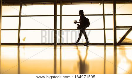 The girl with cup of coffee going in airport in front of window opposite the runway, silhouette, warm, wide angle