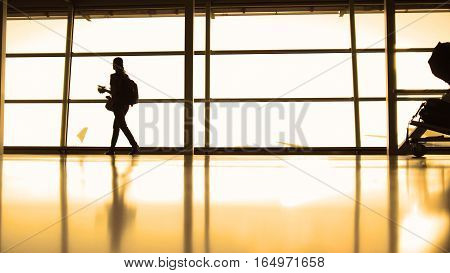 The girl with the backpack with glasses going in airport in front of window opposite the runway, silhouette, warm, wide angle
