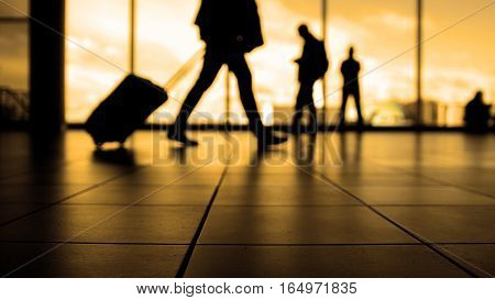 Travellers in airport walking to departures by escalator in front of window, silhouette, warm, wide angle