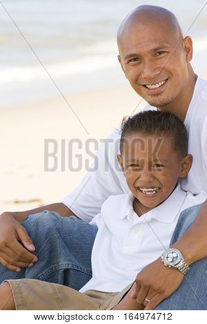 Asian father and son smiling on the beach.