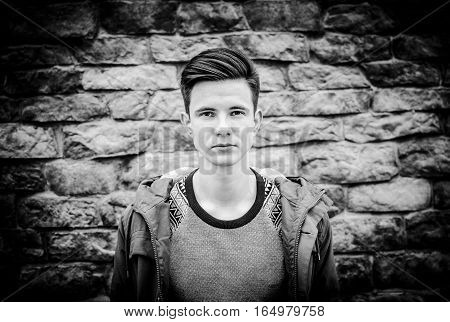 Black and white photo portrait of the young man on the wall background