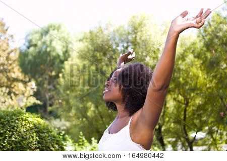 African American woman with her hands raised.