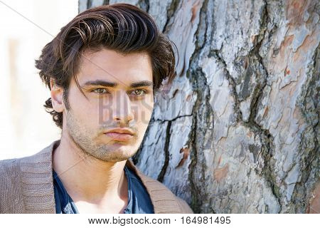 Handsome young man portrait near a tree with stylish hair.