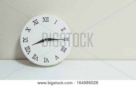 Closeup white clock for decorate show a quarter past eight or 8:15 a.m. on white wood desk and cream wallpaper textured background with copy space