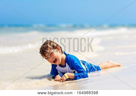Adorable little blond kid boy having fun on tropical beach of Maldives. Excited child playing and surfing in sun protected swimsuit in ocean on vacations.