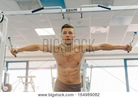 close up photo of attractive man training on Fitness-station. Guy with six-pack abs and strong hands. He working out to become jacked, develop strength, develop definition of muscles