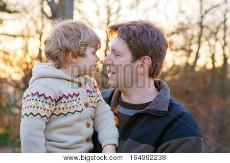 Father and little son in park or forest, outdoors. Hugging and having fun together.
