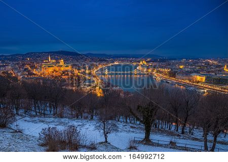 Budapest Hungary - Panoramic skyline view of the Buda Castle (Royal Palace) Chain Bridge Danube River and the Parliament at blue hour as seen from Gellert Hill in winter time
