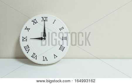Closeup white clock for decorate show 9 o'clock on white wood desk and cream wallpaper textured background with copy space