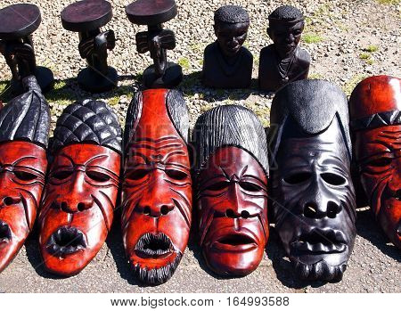 Hazyview, South Africa - April 25, 2014: African handmade ritual tribal wooden masks souvenirs and Nelson Mandela busts on the local craft market in the Hazyview, South Africa. Modern tribal art.