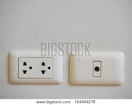 TV outlet or cable outlet and electronic plug socket on wall.