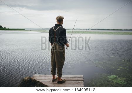 man fisherman catches a fish in the river from the bridge