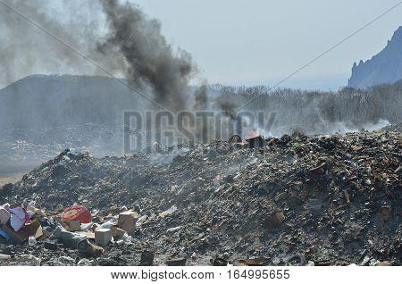 A landscape on scrap-heap in smoke. Russian Far-East.