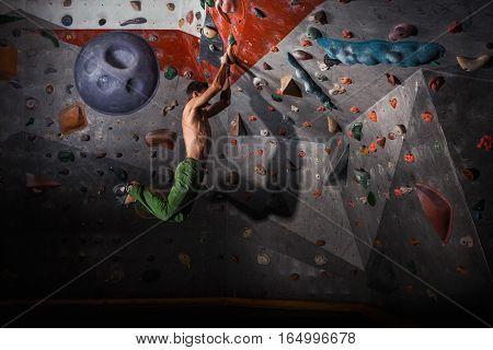 Muscular man practicing rock-climbing on a rock wall indoors