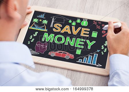 High Angle View Of Businessperson Drawing Save Money Concept On Slate At Wooden Desk