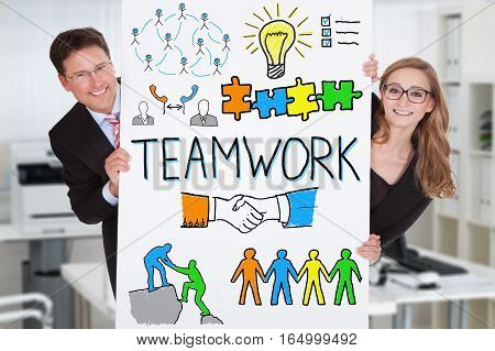 Two Successful Businesspeople Hiding Behind The White Chart Showing Teamwork Concept In Office