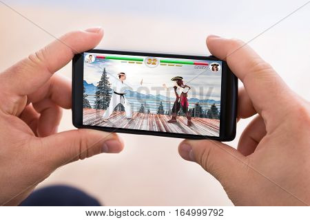 Close-up Of Person Hand Playing Fighting Game On Smartphone